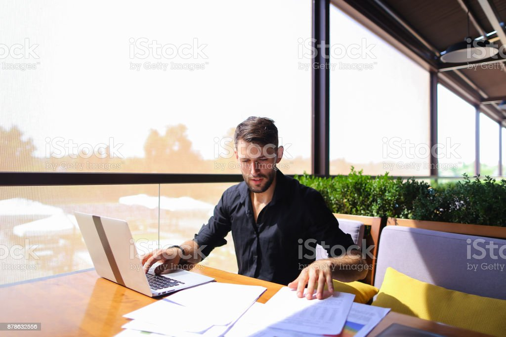 Office worker sorting papers on table near laptop stock photo