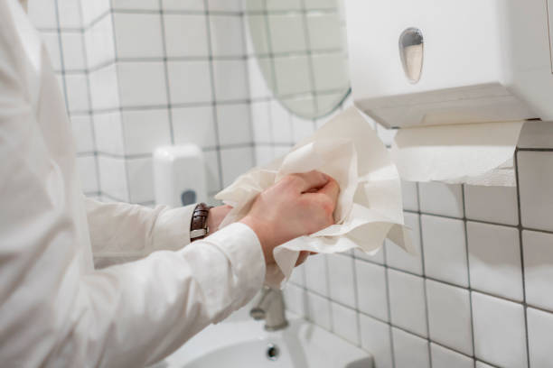 office worker take paper towel after washing his hands stock photo