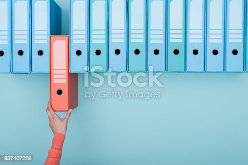 Office worker taking an highlighted folder in the archive: database, administration and file management concept