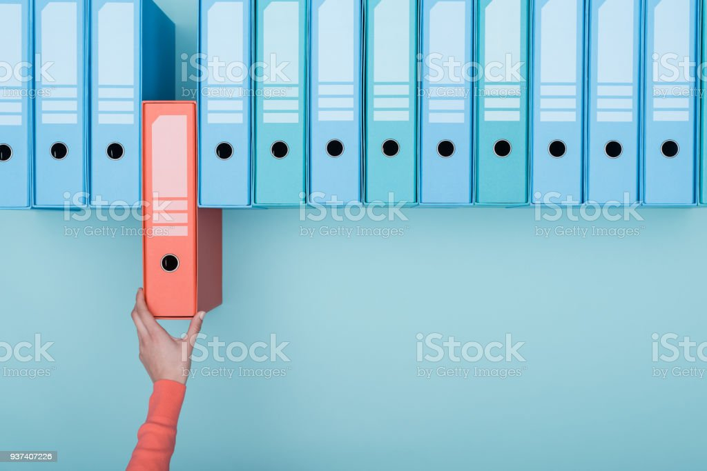 Office worker taking a folder in the archive stock photo