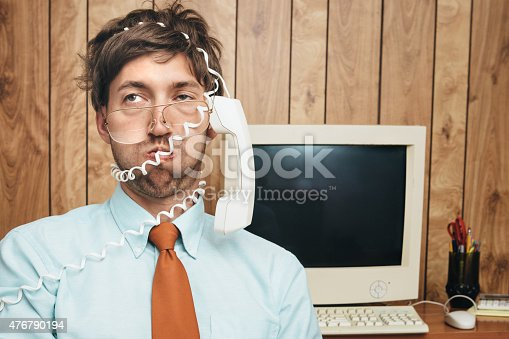 A man and office in 1980's - 1990's style, complete with vintage computer and technology of the time, looks exhausted and perplexed, his phone cord wrapped around his head and face.  Wood paneling on the wall in the background.  Horizontal image.