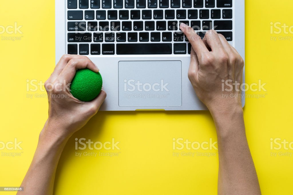 Office worker typing email on computer, feels stressed and nervous, holds a stress ball in her hand stock photo