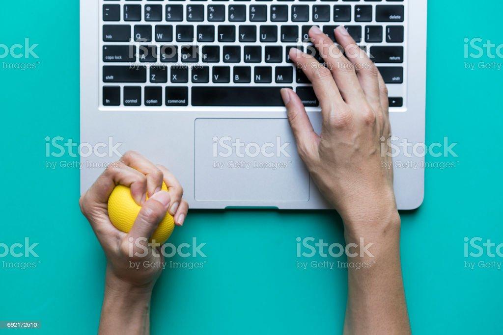 Büroangestellte, die e-Mail zu schreiben, am Computer, fühlt sich gestresst und nervös, hat einen Stress-Ball in der hand – Foto