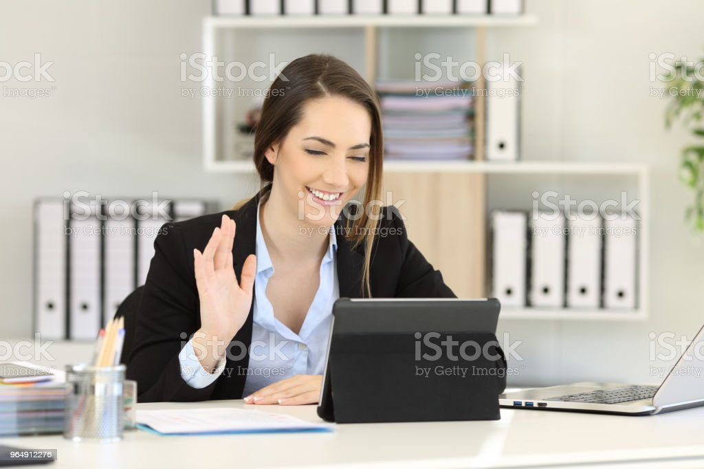 Office worker waving in a video conference with a tablet royalty-free stock photo