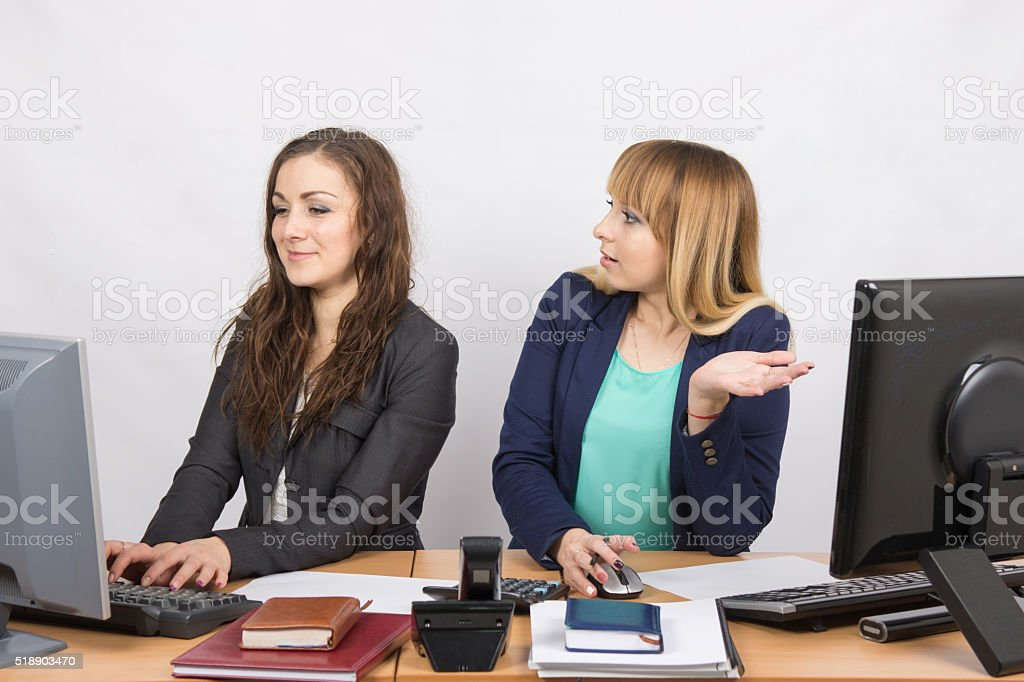Office worker with indignation looking quite colleague sitting next computer stock photo