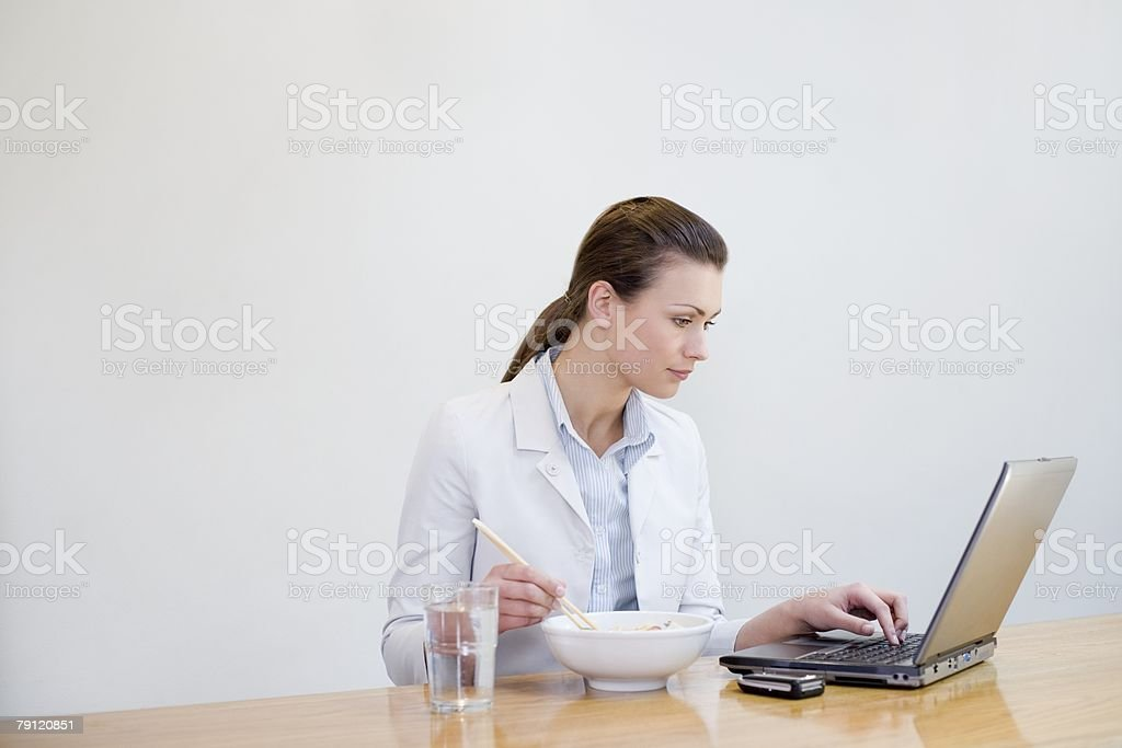 Office worker with lunch and laptop royalty-free stock photo