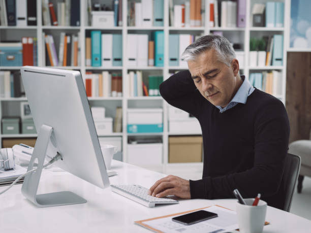 Office worker with neck pain Office worker sitting at desk and having neck pain, he is massaging his neck: stress and overwork concept bad posture stock pictures, royalty-free photos & images