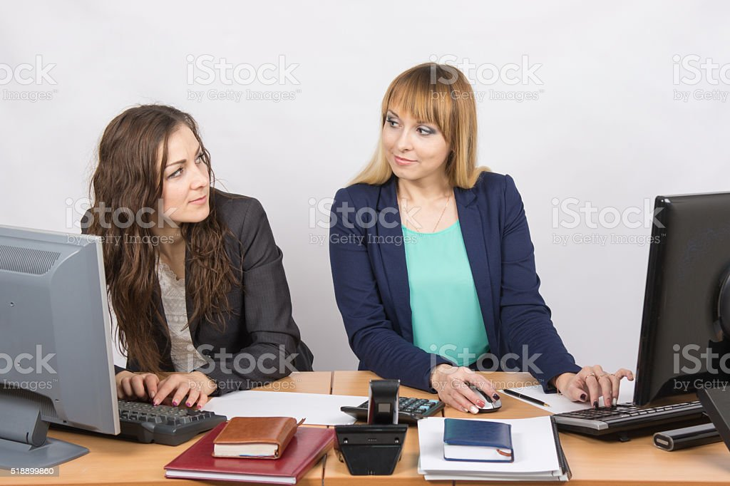 Office worker with superior looks at grim colleague sitting next stock photo