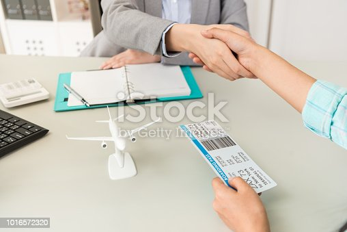 close up of travel agent company office worker with traveler customer handshake when they finished deal. selective focus photo.