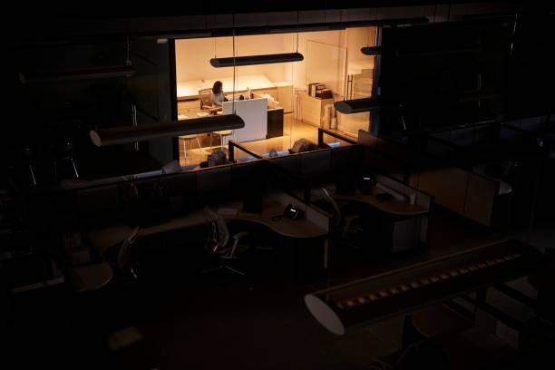 tarde de trabajo en una oficina lo contrario oscura oficinista - trabajar hasta tarde fotografías e imágenes de stock