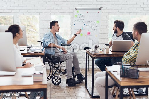 istock Office workers and man in a wheelchair discussing business moments in a modern office. 873015790
