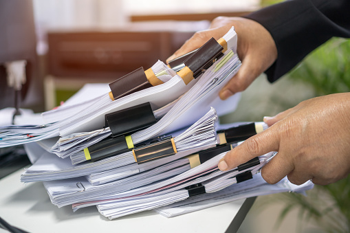 Office workers arranging stacks of lot paperwork files for searching infomation unfinished documents about pile audit form on desk offices and investigate financial doc messy in busy workload