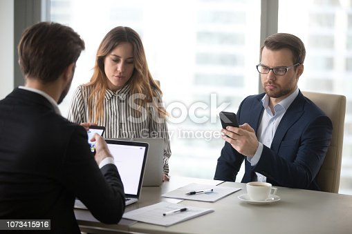 istock Office workers browsing internet, reading online news on break 1073415916