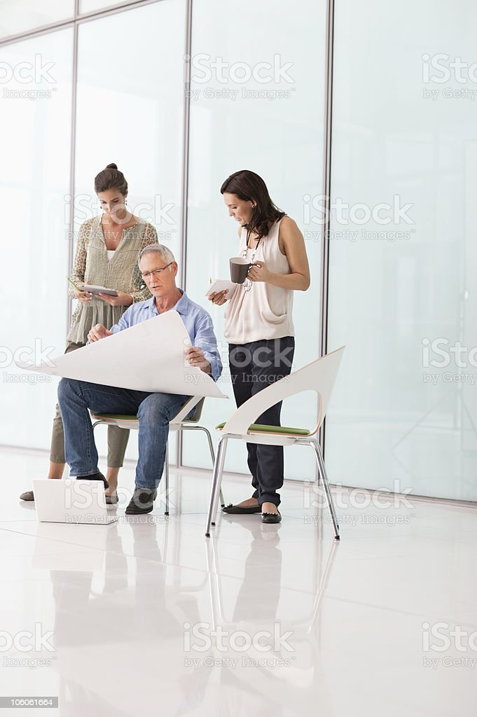 Office workers discussing on blueprint in office royalty-free stock photo