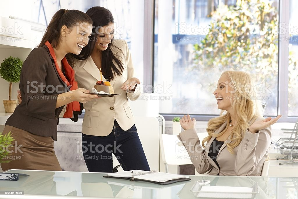 Office workers greeting colleague on birthday royalty-free stock photo