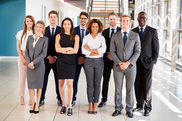 Office workers in a modern lobby, full length group portrait stock photo
