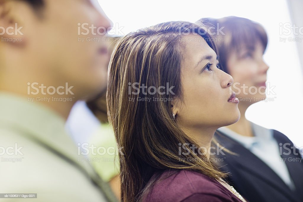 Office workers looking up, focus on woman royalty free stockfoto