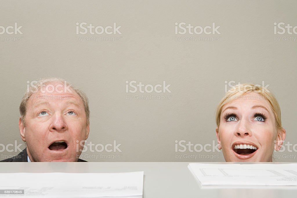 Office workers looking up in surprise stock photo