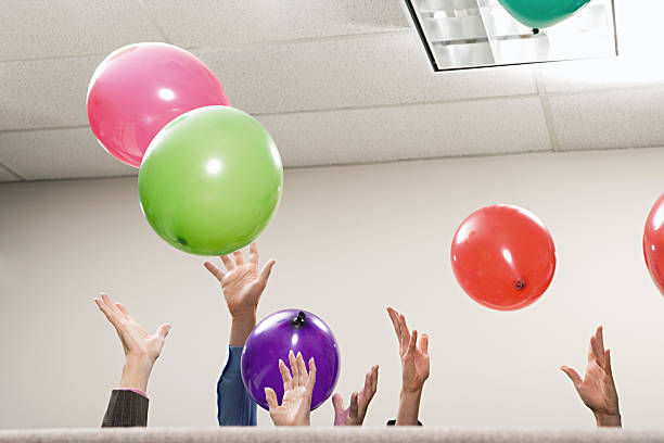 Office workers playing with balloons stock photo