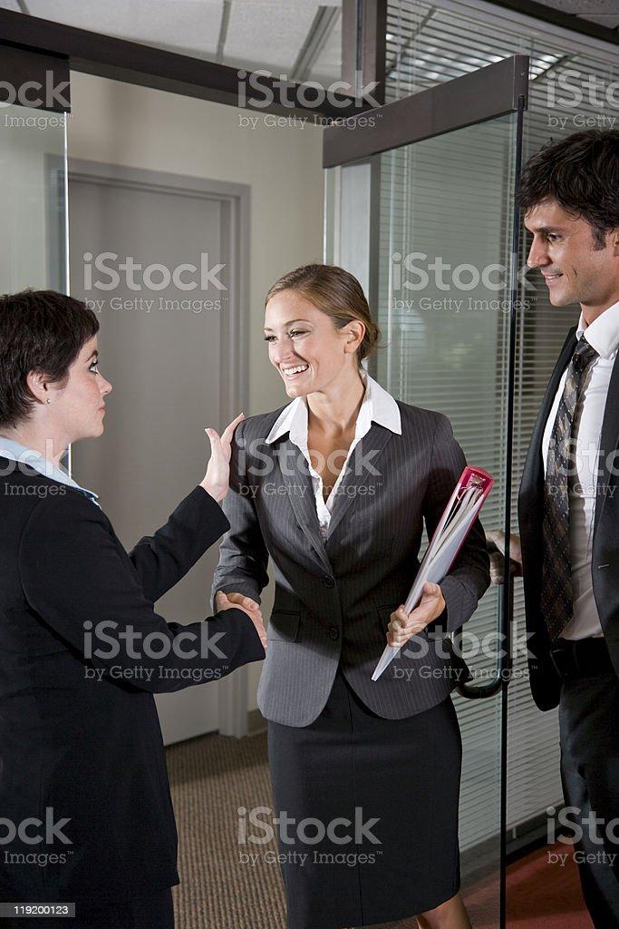 Office workers shaking hands at door of boardroom stock photo