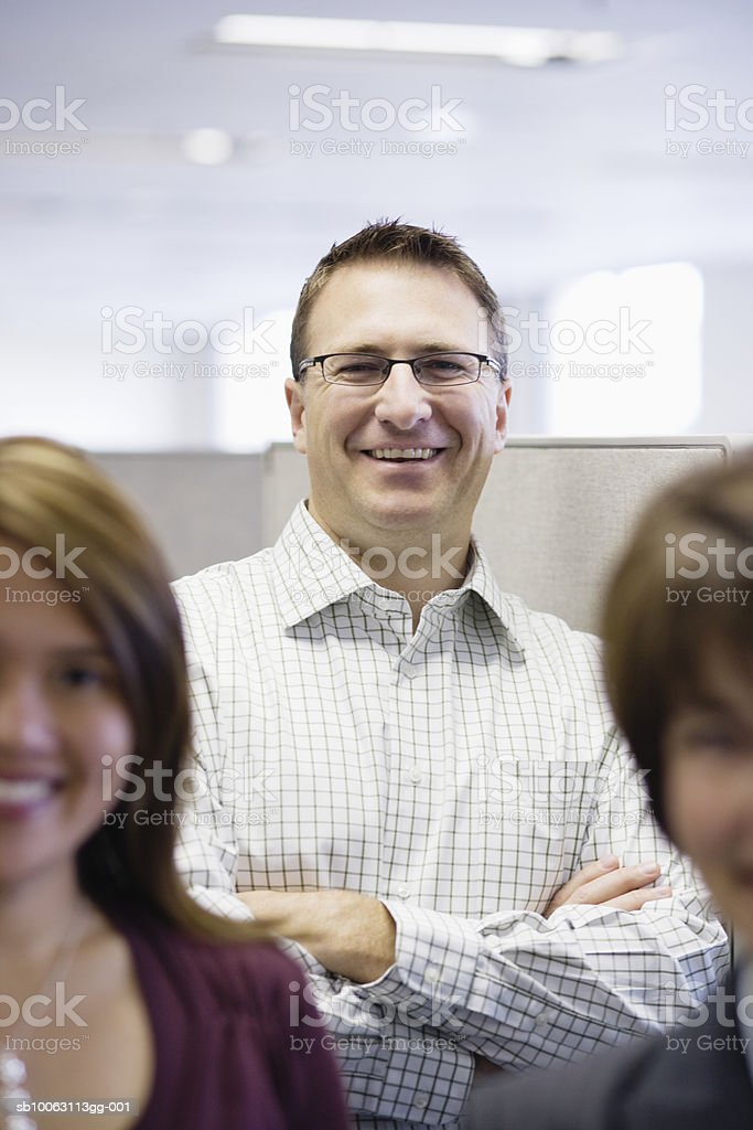 Office workers smiling, focus on man in background foto de stock libre de derechos