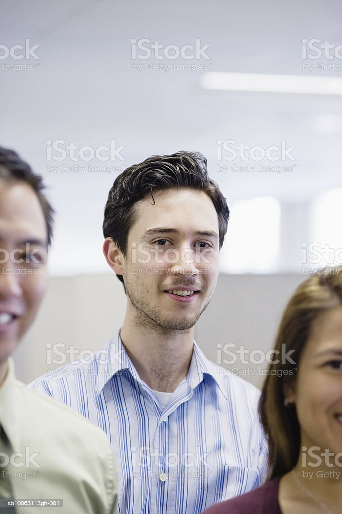 Office workers smiling, focus on man in background royalty-free 스톡 사진