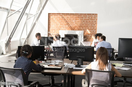 1090214584 istock photo Office workers using computers working at modern big open space 1070271782