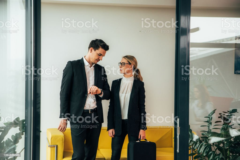 Businessman checking time while waiting at office with female coworker