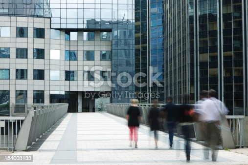 889637894 istock photo Office Workers Walking Down Elevated Walkway Toward Business Building 154003133