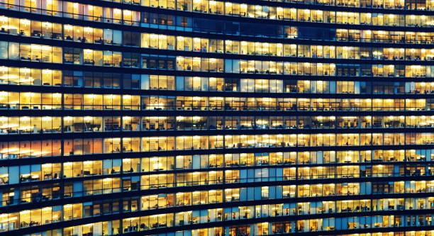Kontorsarbetare som arbetar sent i större kontorsbyggnad bildbanksfoto