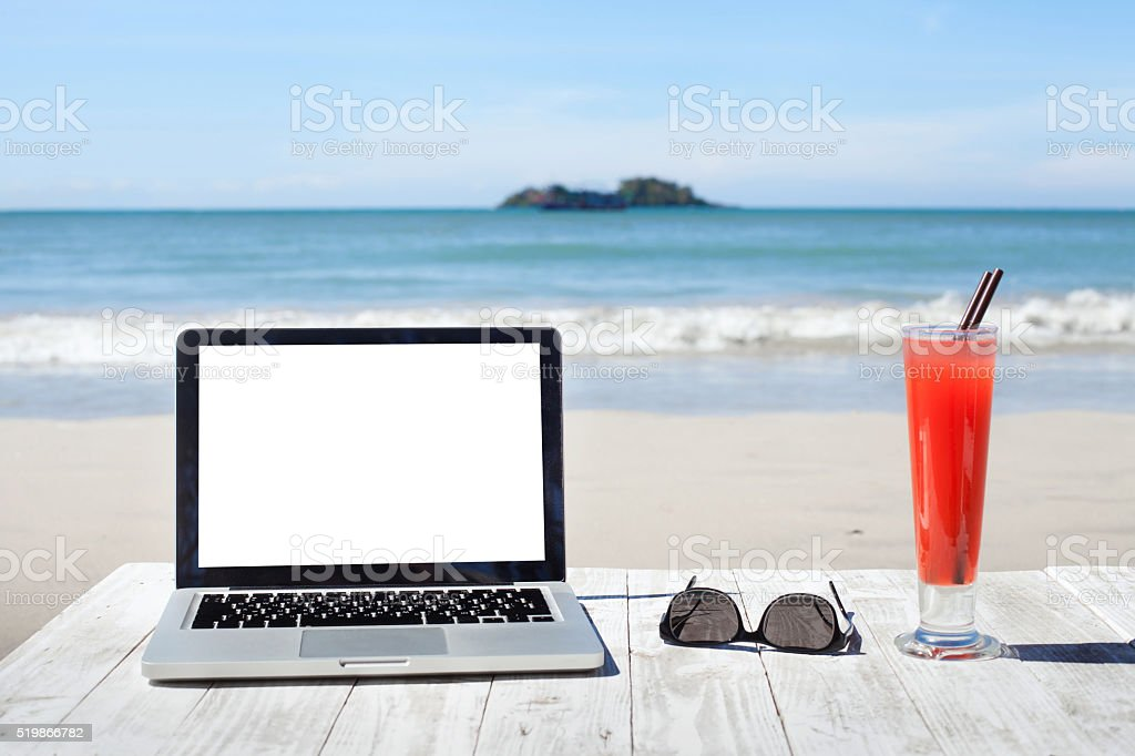 office workplace on the beach, laptop and cocktail stock photo