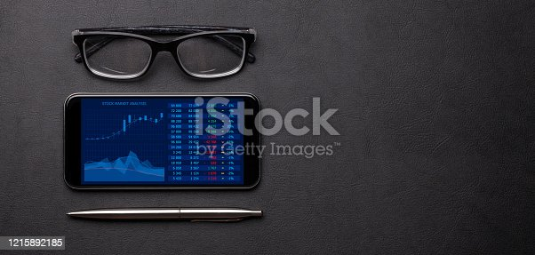 istock Office workplace table with smartphone, glasses and supplies 1215892185