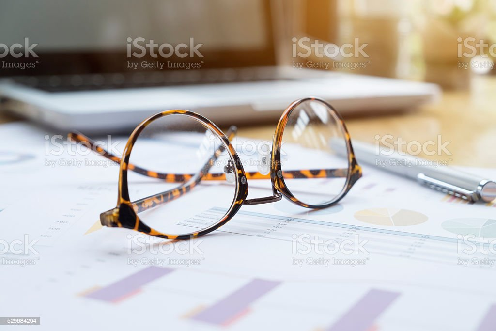 Office workplace with laptop and glasses on wood table. stock photo