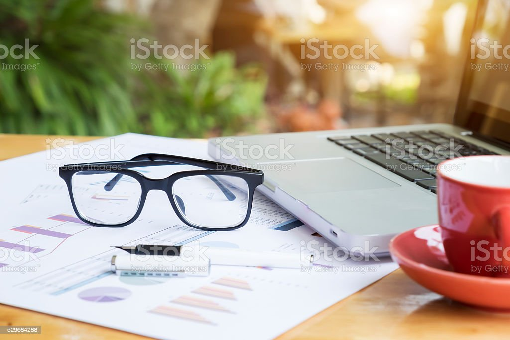Office workplace with laptop and glasses on wood table.