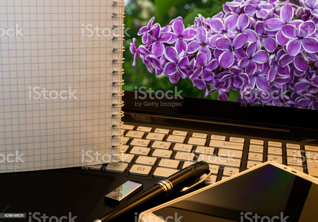 Office workplace with notebook, smart phone, pen, flash drive and wordpad with violet flowers background stock photo