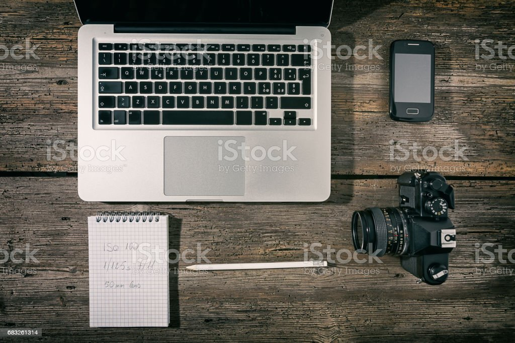 Office workstation with laptop, smartphone, camera, notebook and pencil 免版稅 stock photo