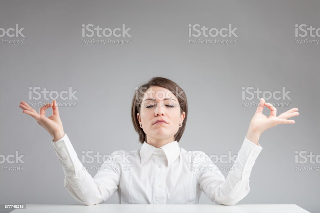 office zen woman relaxing and meditating stock photo