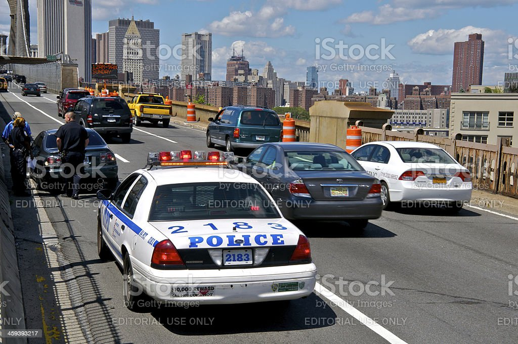 NYPD Officer assists stranded motorist on Brooklyn Bridge, NYC stock photo