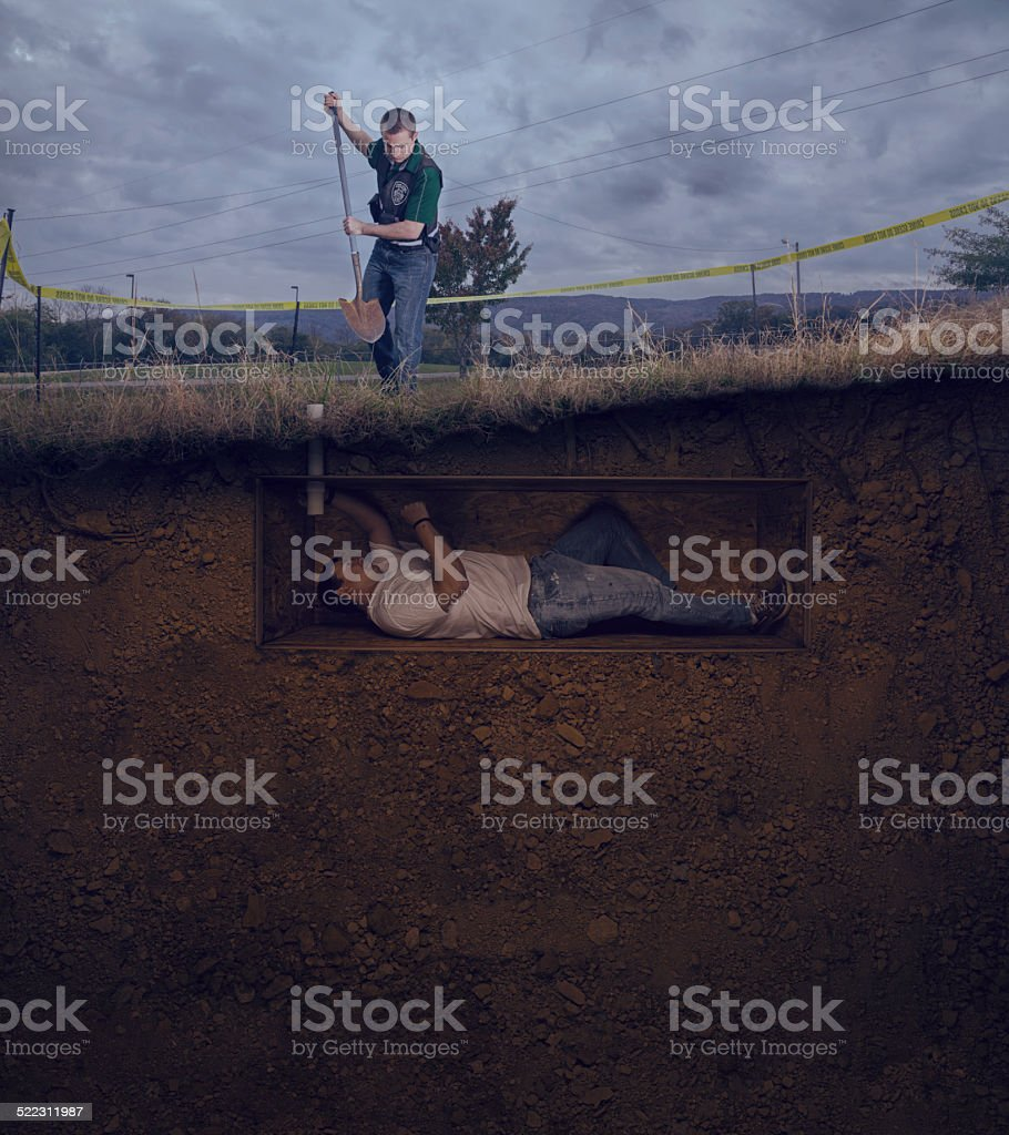 CSI officer to unearth a male victim buried alive stock photo