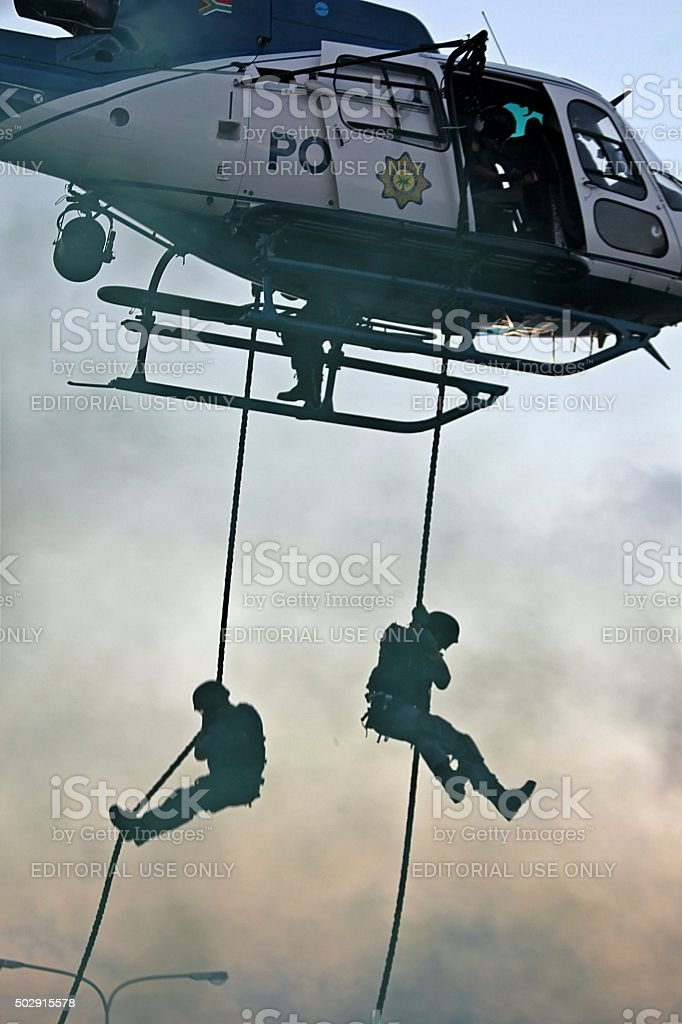 SWAT officers fast-rope from police helicopter stock photo