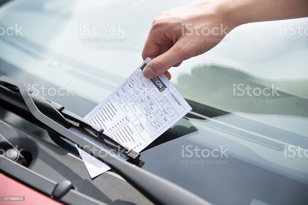 Officer's Hand Putting Parking Ticket On Car stock photo