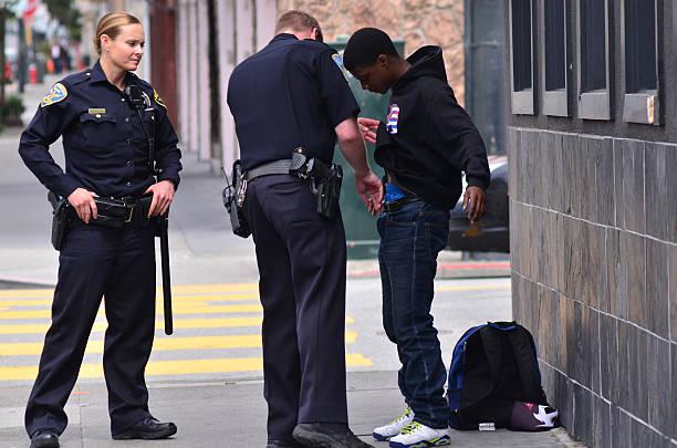 SFPD officers patdown black american man in San Francisco stock photo
