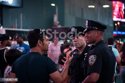 New York City, USA - July 9, 2016: New York City Police Department officers talk with visitors at night in Times Square.