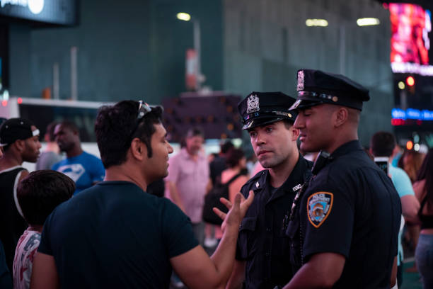 NYPD officers talking with visitors in Times Square stock photo
