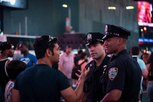 NYPD-Offiziere im Gespräch mit Besuchern auf dem Times Square – Foto