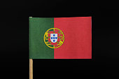 A official and original flag of Portugal on toothpick on black background.