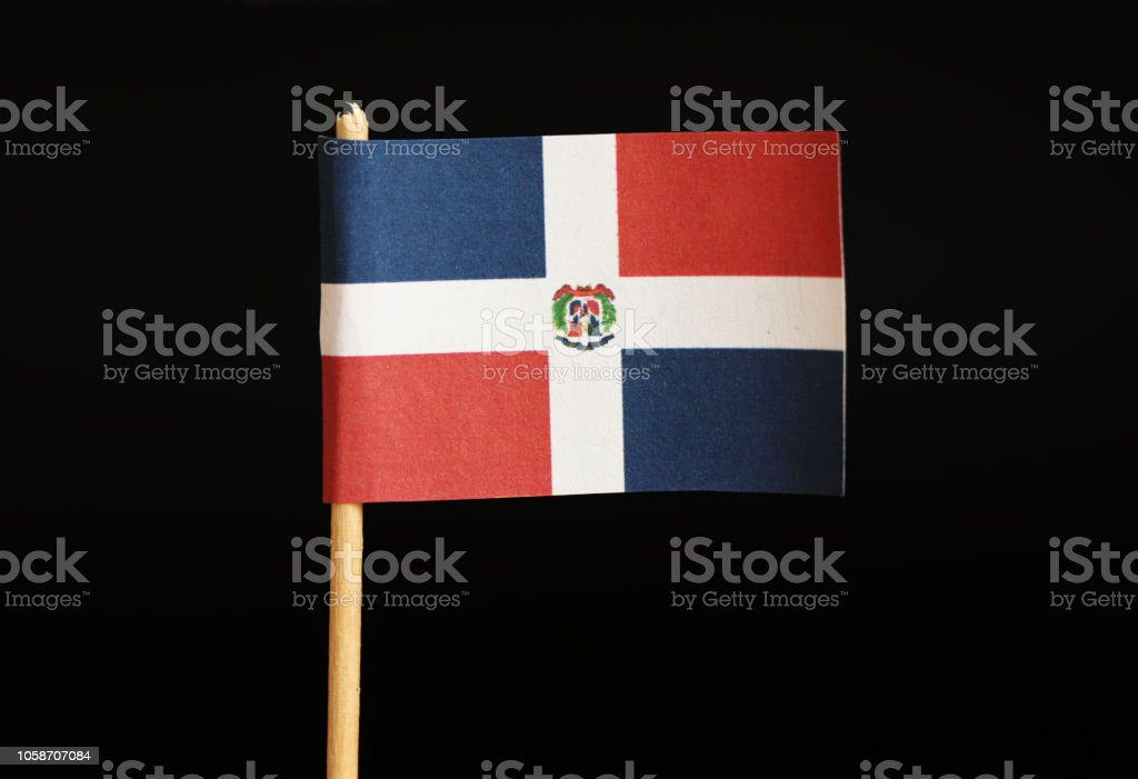 A official flag of dominican republic on toothpick on black background. It is hand flag represented your country. stock photo