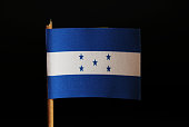 A official flag of Honduras on toothpick and on black background. Honduras is located in central america and belongs to poverty lands