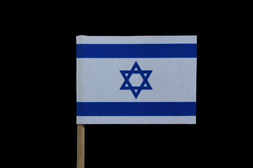 istock A official flag of Israel on toothpick on black background. A blue Star of David between two horizontal blue stripes on a white field. 1081868828
