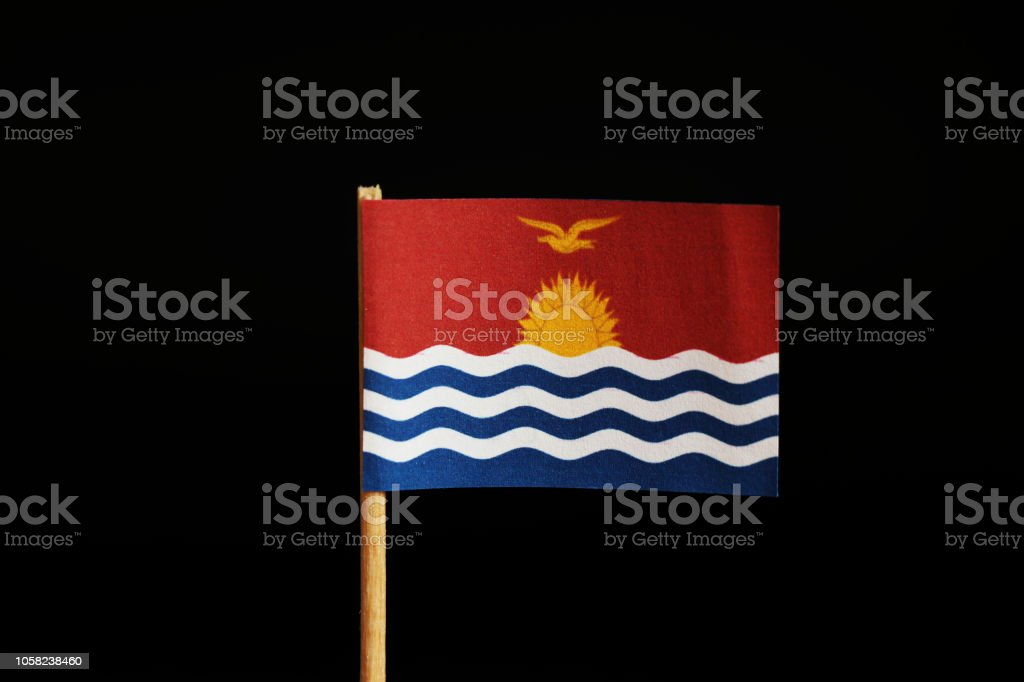A official Flag of Kiribati on wooden stick on black background. State in the middle Oceania, pacific ocean. stock photo